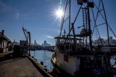 Fishermans-Kai, der die Sonne mit der Stadt im Hintergrund untersucht lizenzfreie stockbilder