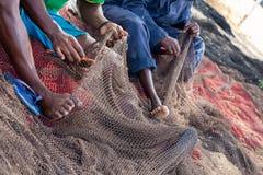 Fishermans mending nets. Burgundy, black, white, gray. Fishermans mending nets. Fishing nets. Floats on the fishing net stock image