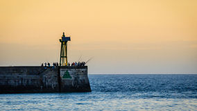 Fishermans next to a lighthouse Royalty Free Stock Images