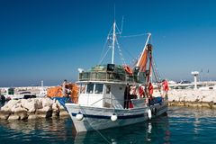 Fishermans prepare boat to sai. Few fishermans prepare shrimp boat to sail out stock images