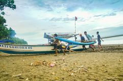 Fishermans pushing their boat to the beach. wide low angle view stock images