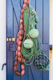 Fishermans rope and floats hanging on a blue door Royalty Free Stock Photos