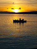 Fishermans and sea gulls in sunset Royalty Free Stock Image