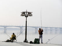 Fishermans sits on municipal embankment and fishes. Two fishermen sit on a municipal embankment and fish, spring, Dnipropetrovsk, Ukraine Stock Images