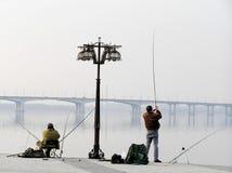 Fishermans sitzt auf städtischem Damm und Fischen Stockbilder