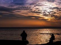 Fishermans sur le bord de la mer calme de coucher du soleil Photographie stock libre de droits