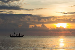 Fishermans are working in sunrise. On the sea Royalty Free Stock Images