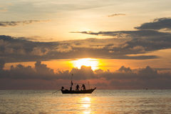 Fishermans are working in sunrise. On the sea Royalty Free Stock Image