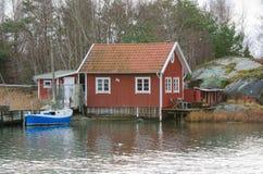 Fishermansbotenhuis en boot met pijler Stock Afbeelding