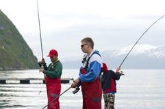 Fishermen. Three fishermen fishing in a Norwegian fjord royalty free stock image