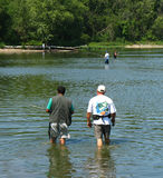 Fishermen. Wading in river carrying fishing poles Stock Image