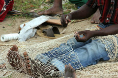 Fishermen. Hands and feet of a fisherman in Kenya while mending its networks royalty free stock photo