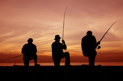 Fishermen. Three silhouetted fishermen with their fishing rods at sunset Stock Photos