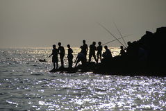 Fishermen. With  fishing rods on the sea Stock Photo