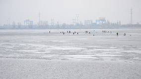 Fishermen angling on ice on background of electric. Many winter fishermen angling on ice of partly frozen water storage reservoir on background of hydro electric stock video footage