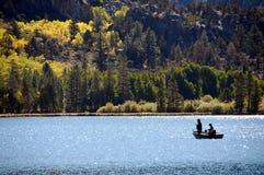 Fishermen and aspens. Fishermen on a lake surrounded by aspen grove Stock Image