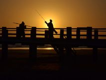 Fishermen. Backlit fishermen on the pier during sunrise Stock Photos