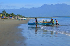 Fishermen. Baler, Aurora, PHilippines – June 23,1 2014: Fishermen returning from sea with their boat stock images