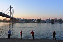 Fishermen on the bank of a river Stock Photography