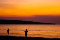 Fishermen on the beach on the island of Bali at sunset. stock photos