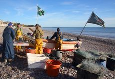 Fishermen on the beach selling fish in south devon stock photos