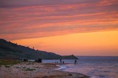 Fishermen on the beach at purple sunset