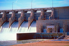 Fishermen below the dam. Fishermen dwarfed below the flowing spillway of the dam stock photography