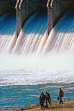 Fishermen below the spillway. Three fishermen dwarfed by the size of the dam spillway royalty free stock images