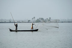 Fishermen in a boat catch fish by throwing net in to the backwaters Royalty Free Stock Image