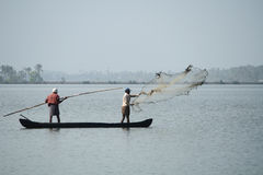Fishermen in a boat catch fish by throwing net in to the backwaters Royalty Free Stock Photos