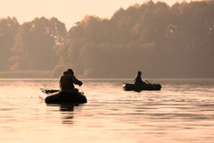 Fishermen in a boat catching fish early in the morning Stock Image