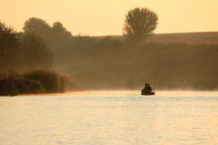 Fishermen in a boat catching fish early in the morning Royalty Free Stock Image