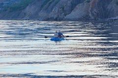 Fishermen by boat fish on lake Stock Photo