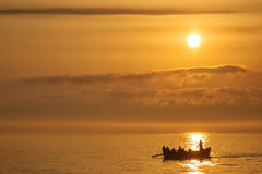 Fishermen on a boat fishing on a sea with beautiful sunrise in b. Ackground royalty free stock photography