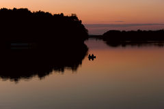 Fishermen on a boat floating on the lake after sun Royalty Free Stock Images