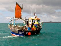 Fishermen in a boat, Isles of Scilly, Cornwall England. Isles of Scilly, United Kingdom – March 18, 2012: Fisherman ply the turquoise sea around the Isles of Stock Photography