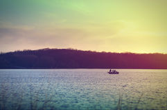 Fishermen on a boat at Lake Macbride after sunset Stock Photo