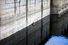 Fishermen in a boat near the Paltinu dam concrete wall, Doftana, Romania. Fishing in a boat near the Paltinu dam concrete wall, Doftana, Romania Royalty Free Stock Image