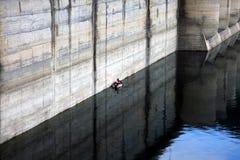 Fishermen in a boat near the Paltinu dam concrete wall, Doftana, Romania Royalty Free Stock Image