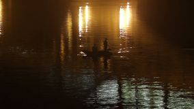 Fishermen boat night timelapse city yellow lights in water shine. Stock footage stock video