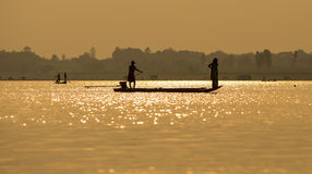 Fishermen in the boat sunrise Stock Photo