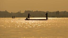 Fishermen in the boat sunrise Stock Photo