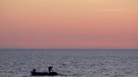 Fishermen on a boat on the sunset sky background throw nets into the sea.  stock video footage