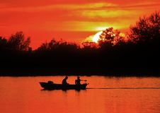 Fishermen boating on a pond. Two boys in a boat on a pond at sunset Royalty Free Stock Images