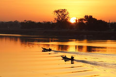 Fishermen on boats. With sunrise silhouette in Ubon Ratchathani Royalty Free Stock Photo