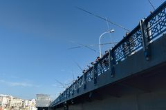 Fishermen on a bridge under clear blue skies stock photos
