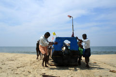 Fishermen bringing their boat to the shore Royalty Free Stock Images