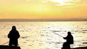 Fishermen on the calm sunset seaside Stock Photography