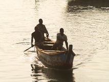 Fishermen in Cape Coast, Ghana, West Africa. Three fishermen in a home made canoe paddle at dusk, their faces hidden in shadow, Cape Coast, Ghana, West Africa Royalty Free Stock Photography