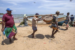 Fishermen carry a basket of fish to the beach to be washed prior to being sold in Negombo, Sri Lanka. They are working in front of the Negombo Fish Market Stock Photography